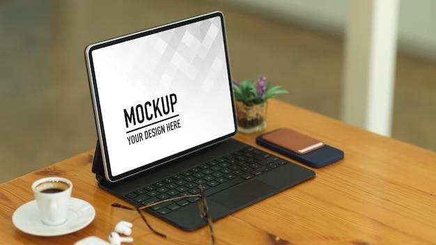 Close-up na mesa de madeira com tablet, teclado, óculos, acessórios e copo no escritório em casa