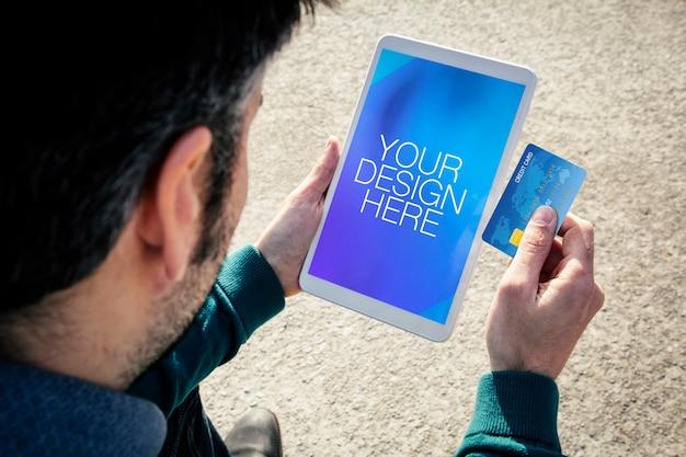 Close-up no homem com maquete de tablet e cartão de crédito