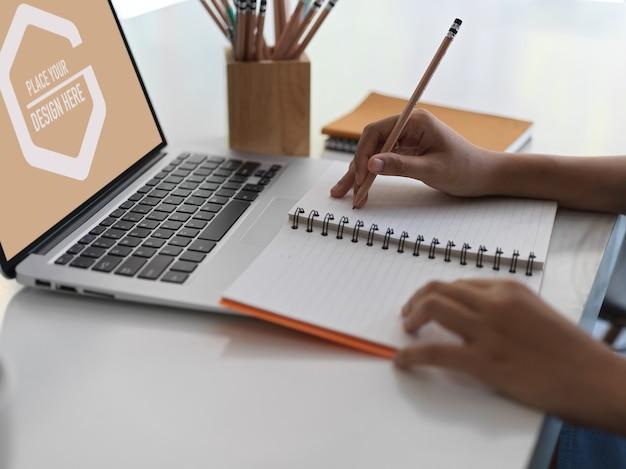 Close-up vista do trabalhador de escritório escrevendo no notebook enquanto usa a tela do laptop