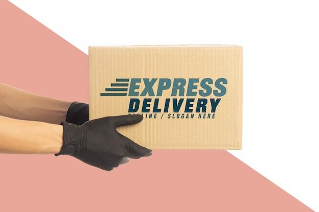 Closeup entrega homem mão em luvas médicas segurando modelo de maquete de caixa de papelão.