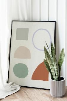 Cobra em um vaso cinza ao lado de uma maquete de porta-retrato