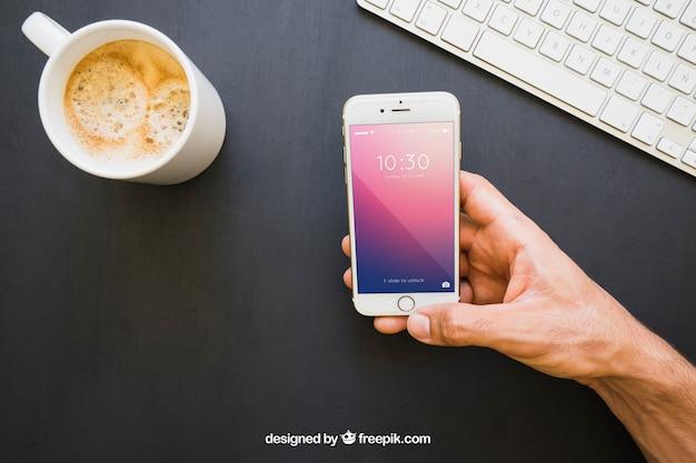 Coffe mug, teclado e mão segurando o telefone
