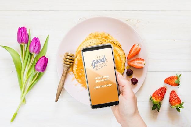 Coleção de panquecas de café da manhã ao lado de smartphone