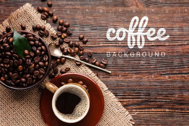 Colher de café e grãos de café sobre fundo de madeira