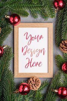 Composição de férias de natal com maquete de moldura. enfeites vermelhos e galhos de pinheiro.