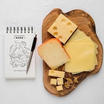 Composição de queijo delicioso com maquete de bloco de notas