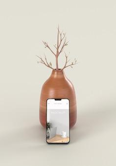 Composição elegante com maquete de smartphone e vaso