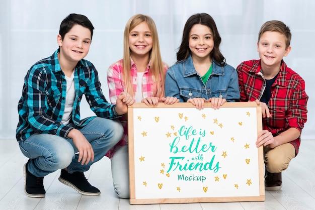 Comunidade de crianças segurando placa de maquete juntos
