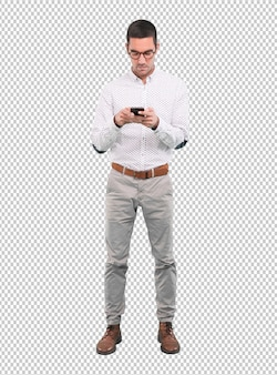 Concentrado jovem usando um smartphone - tiro de corpo inteiro