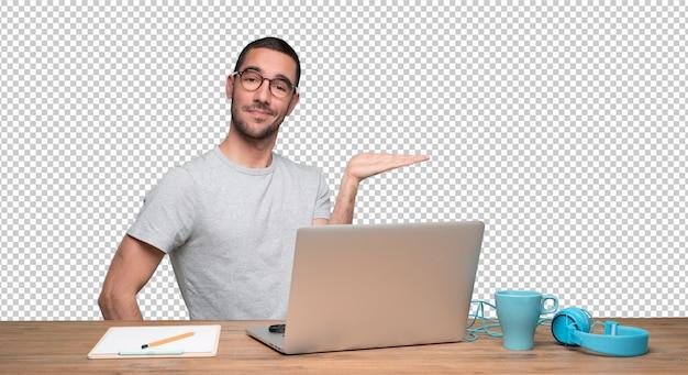 Confiante jovem sentado em sua mesa com um gesto de mostrar algo