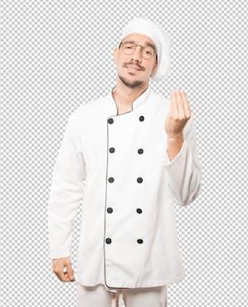Confuso jovem chef fazendo um gesto italiano de não entender