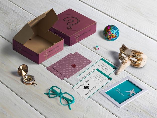 Conjunto de elementos, caixa de papelão, máscara de carnaval, óculos de sol, cartões, bússola, quadro