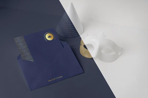 Convite de carnaval de alto ângulo em envelope com máscara e cone