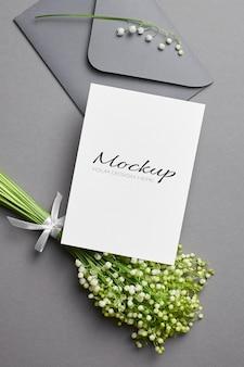 Convite de casamento ou maquete de cartão com envelope e buquê de flores de lírio do vale