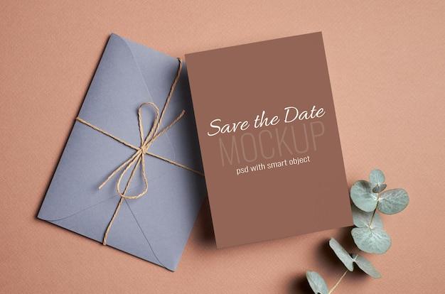 Convite de casamento ou maquete de cartão comemorativo com envelope e galho de eucalipto