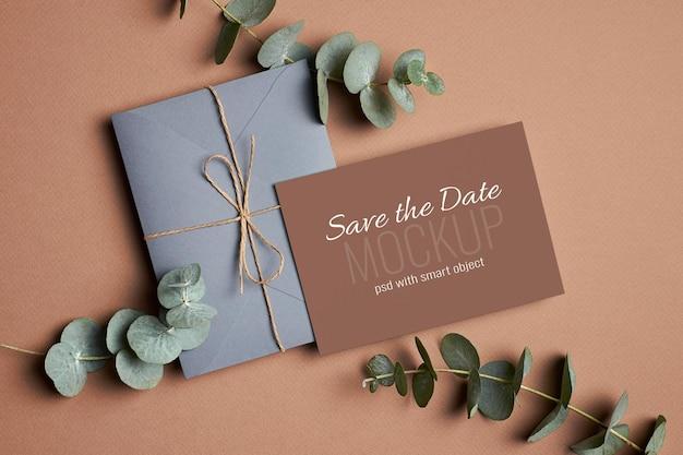 Convite de casamento ou maquete de cartão comemorativo com envelope e galhos de eucalipto