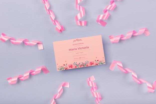 Convite de quinze aniversários rodeado por fitas cor de rosa