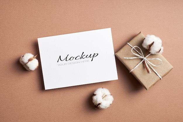 Convite estacionário ou maquete de cartão comemorativo com caixa de presente e flores naturais de algodão