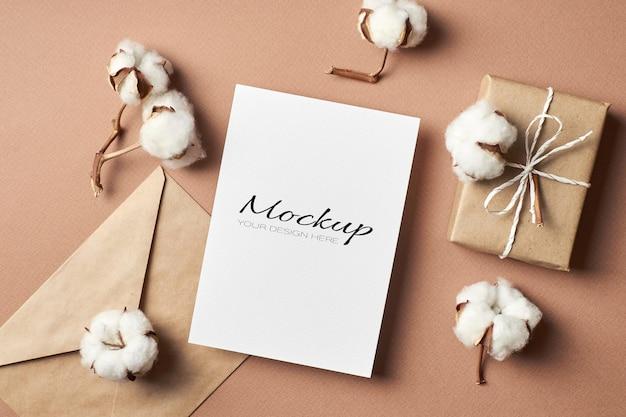 Convite estacionário ou maquete de cartão comemorativo com envelope, caixa de presente e flores naturais de algodão