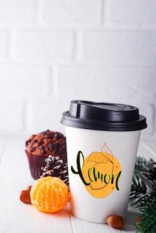 Copo de papel de café rodeado de decorações de natal
