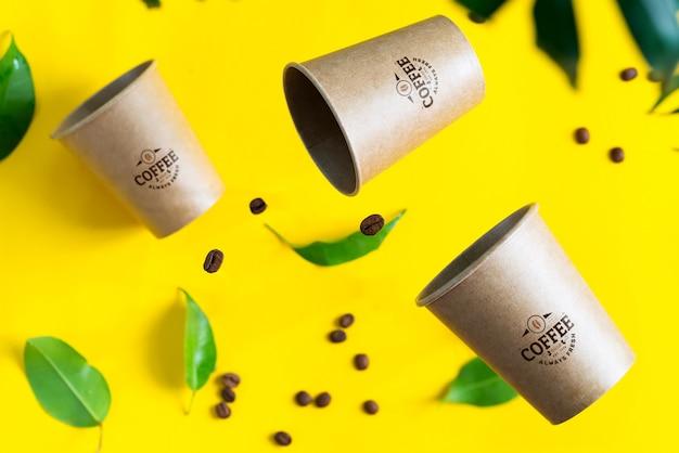 Copos de maquete flutuante com grãos de café e folhas