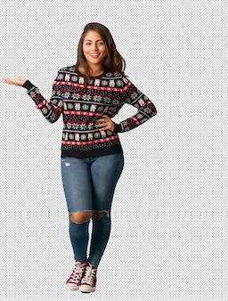 Corpo inteiro, mulher jovem, desgastar, um, natal, jersey, segurando, algo, com, mão