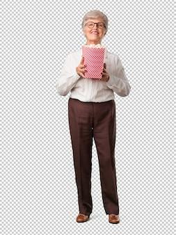 Corpo inteiro mulher sênior feliz e fascinado, segurando um balde de pipoca listrado, surpreso com o novo filme, olhos abertos e expressão de admiração