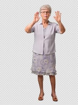Corpo inteiro, mulher sênior, sério, e, determinado, pôr mão, frente, parada, gesto, negar, conceito
