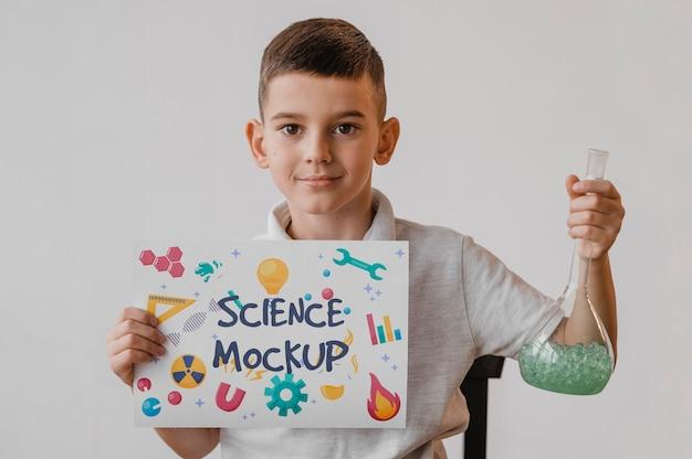 Criança segurando um modelo de cartão enquanto aprende ciências