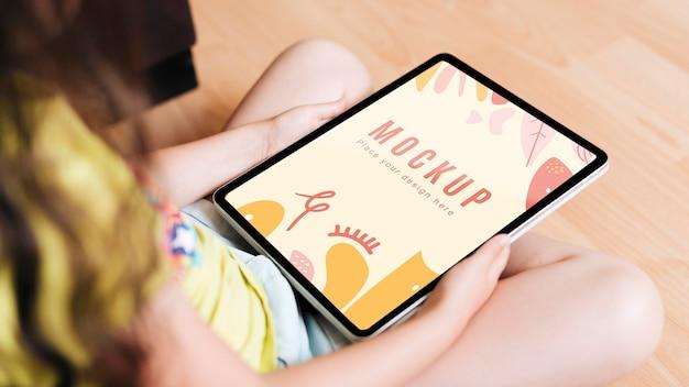 Criança segurando uma maquete digital de tablet