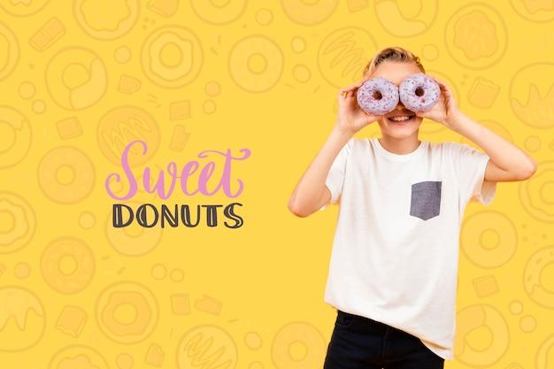 Criança sorridente posando com donuts sobre os olhos