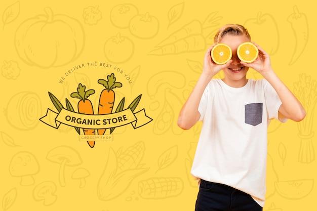Criança sorridente posando com laranjas sobre os olhos