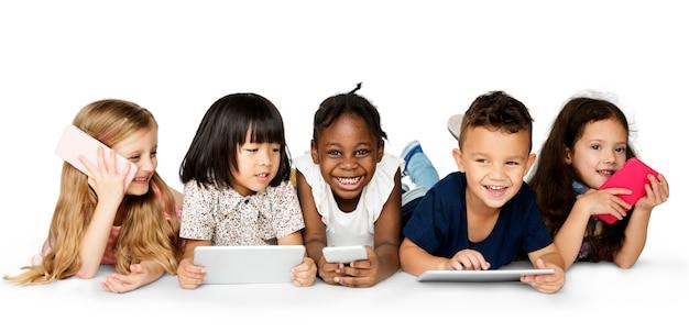 Crianças alegres segurando dispositivos digitais