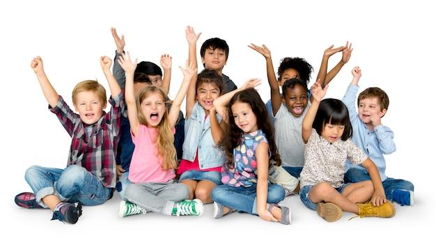 Crianças alegres, tendo um ótimo tempo junto com as mãos levantadas