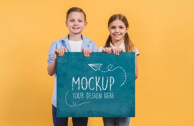 Crianças felizes de frente segurando cartaz com maquete