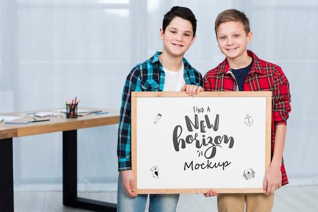 Crianças felizes, segurando placa de maquete