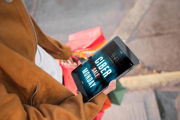 Cyber segunda-feira mockup com mulher segurando o tablet