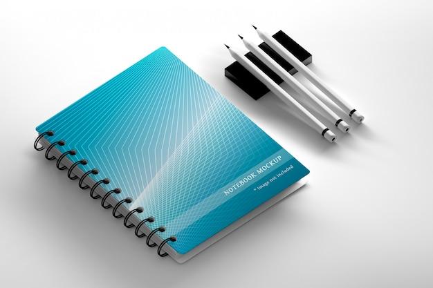 De capa de caderno espiral e três lápis de carbono na superfície branca