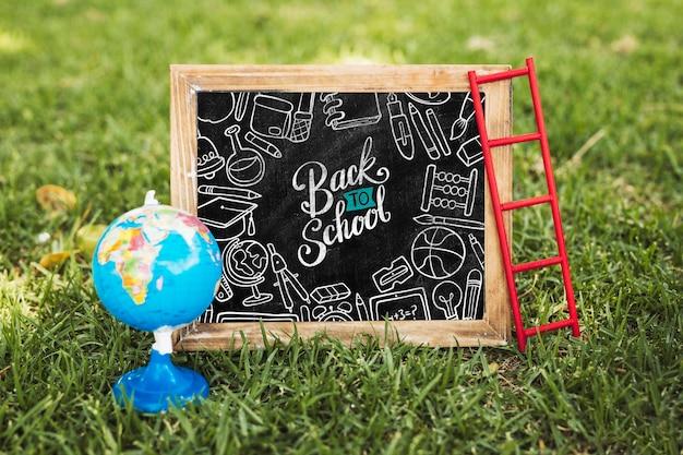 De volta ao quadro-negro da escola ao lado do globo da terra mock-up