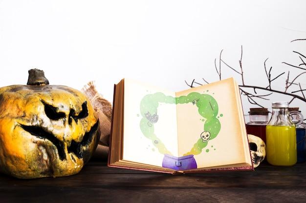 Decoração de abóbora esculpida assustadora e livro com desenho de panela