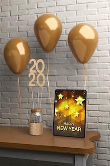 Decorações na mesa ao lado do tablet com mensagem para o ano novo