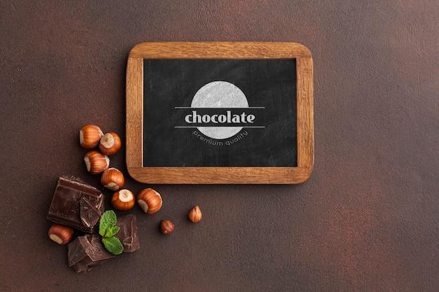 Delicioso chocolate com modelo de quadro-negro sobre fundo marrom