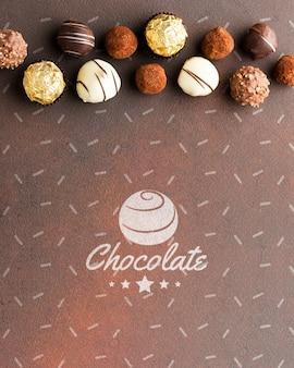 Deliciosos bombons de chocolate com maquete de fundo marrom