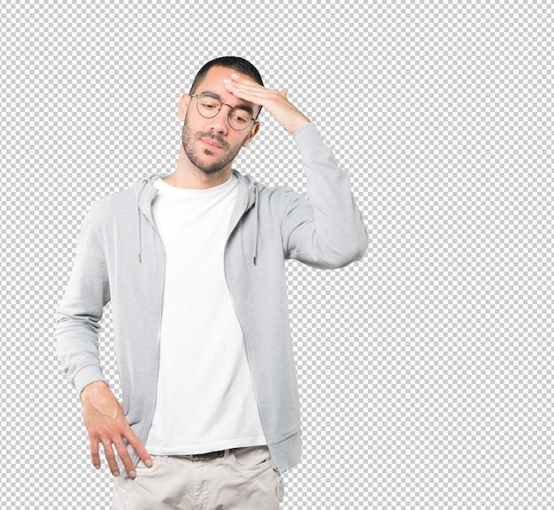 Deprimido jovem posando contra superfície transparente