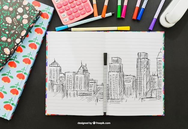 Desenho de edifícios, marcadores, grampeador e calculadora