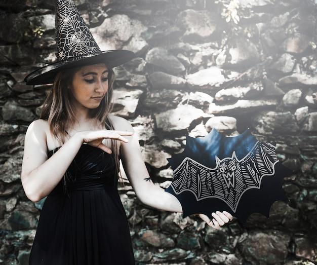 Desenho morcego e mulher vestida como uma bruxa