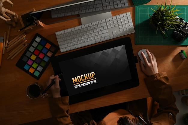 Designer gráfico feminino trabalhando com ferramentas de design e tablet de desenho de maquete