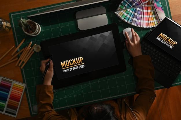 Designer gráfico feminino trabalhando com maquete de desenho de tablet e computador