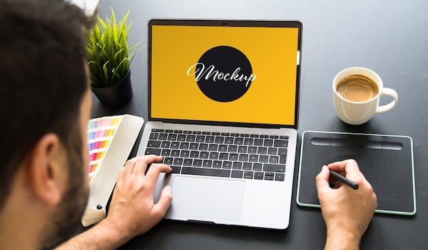 Designer gráfico trabalhando na maquete do laptop