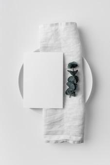 Disposição plana da disposição da mesa com modelo de menu de primavera e toalha no prato
